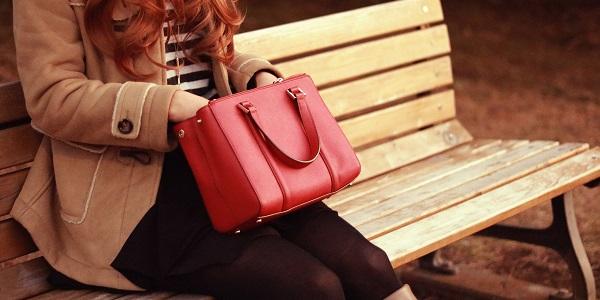 ベンチで赤いバッグの中を探る女性