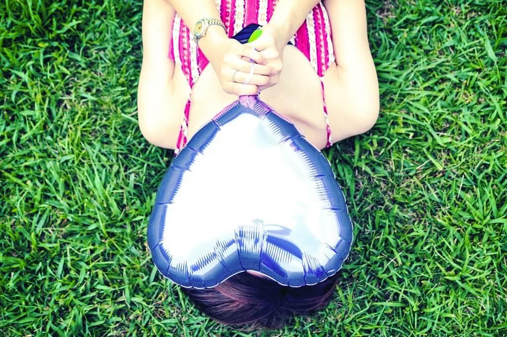 ハートの風船で顔を隠す女性