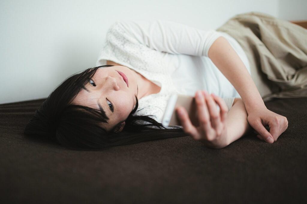寝転んでスマホを操作する女性