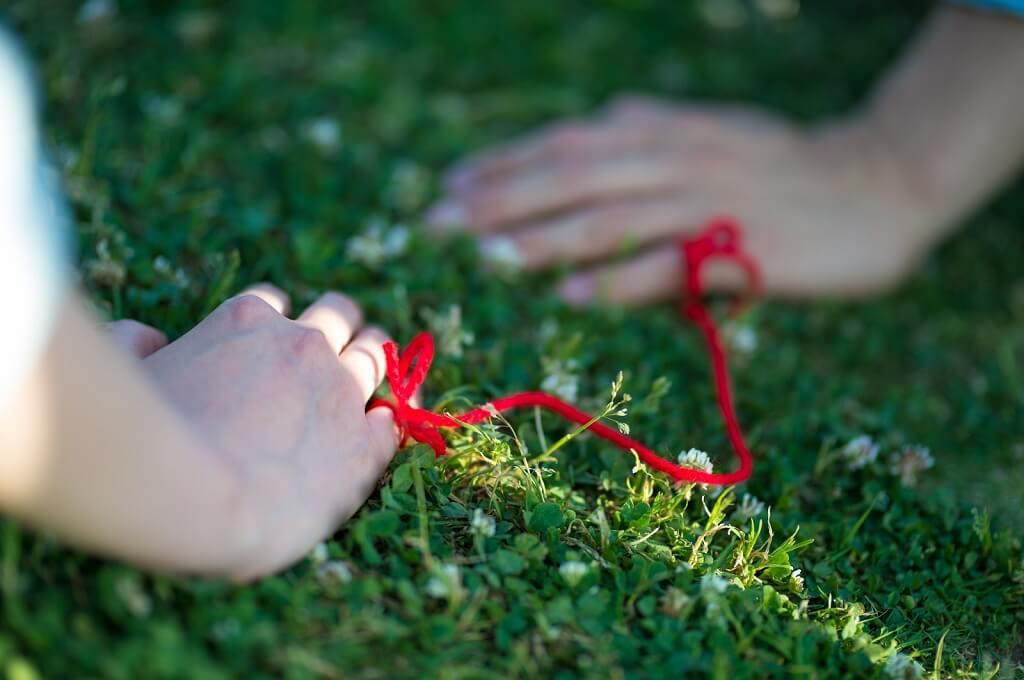 赤い糸で結ばれている手
