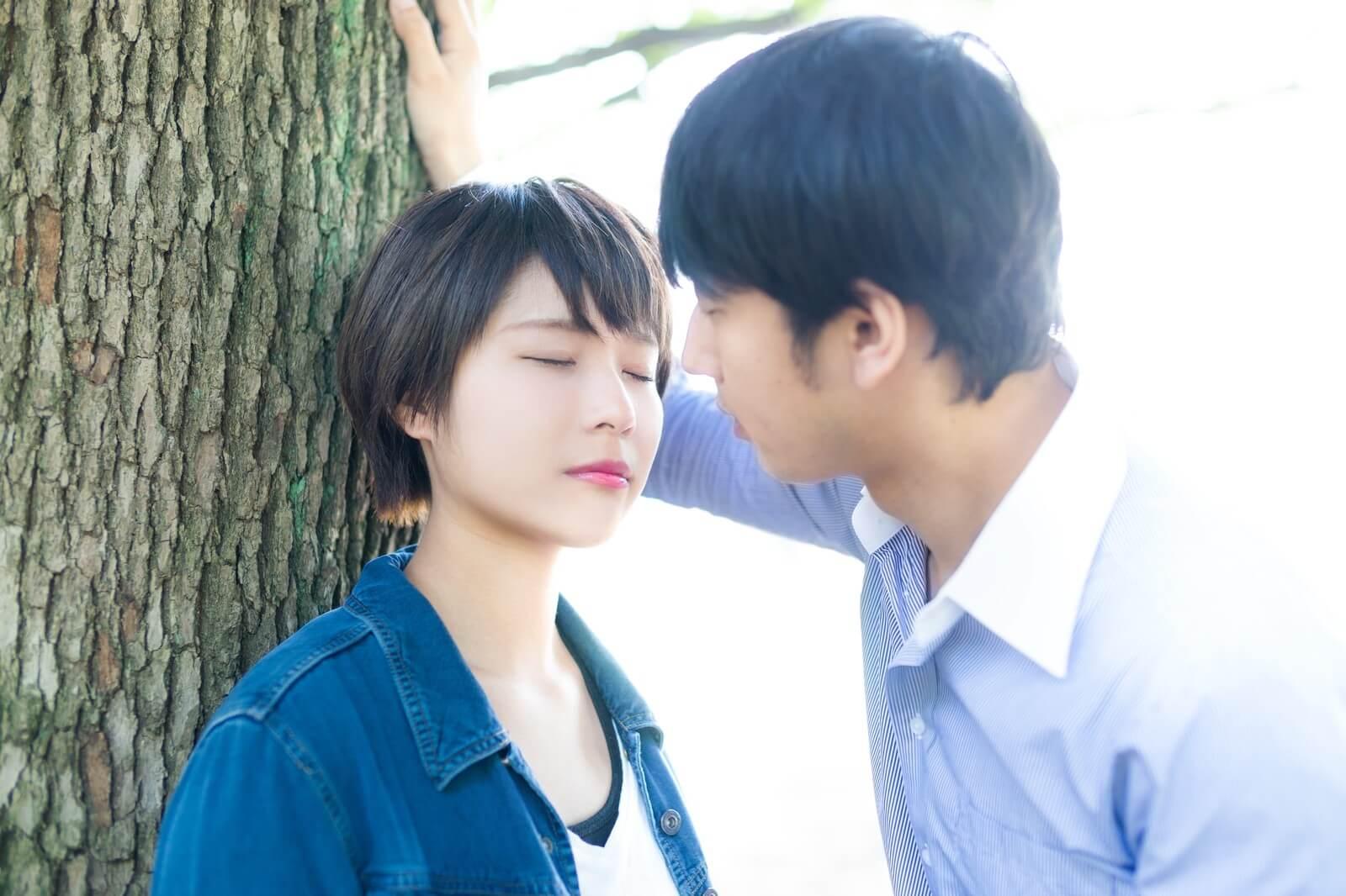 木の下でキスをしようとする男女