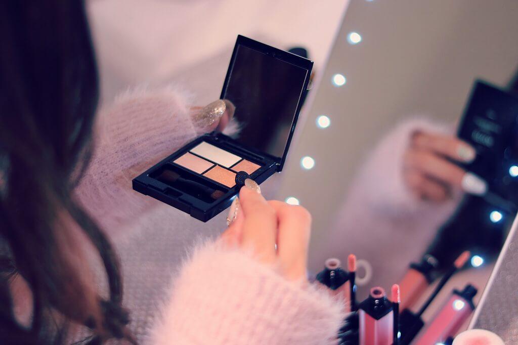 鏡の前で化粧をする女性
