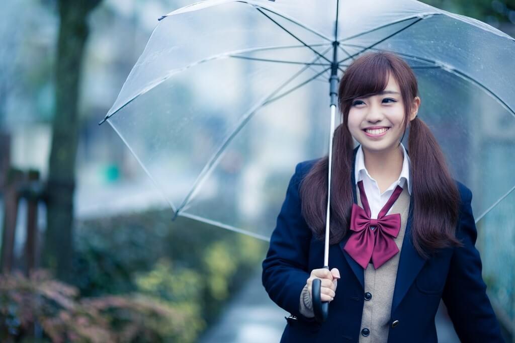 傘を差して楽しそうに歩く女性