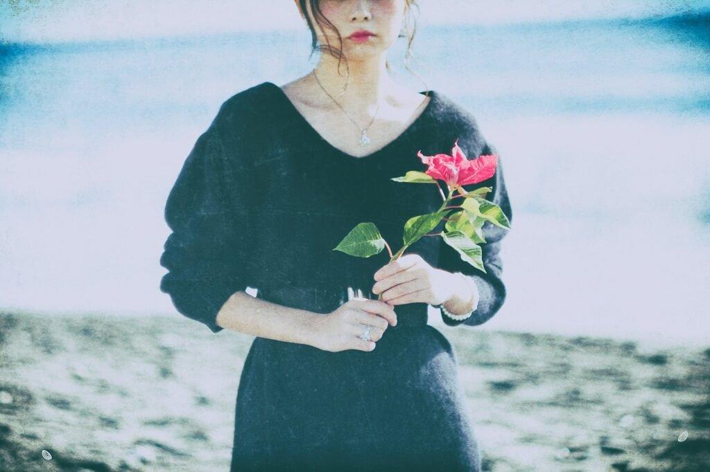 赤い花を持った悲しげな女性