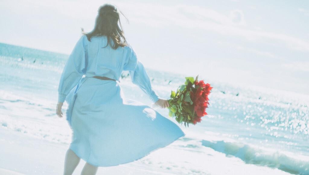 赤い花を持って歩く女性
