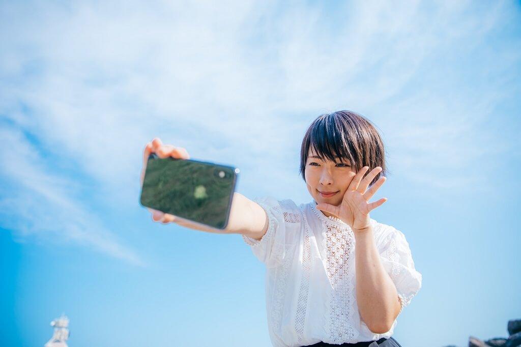 青空をバックに自撮りする女性